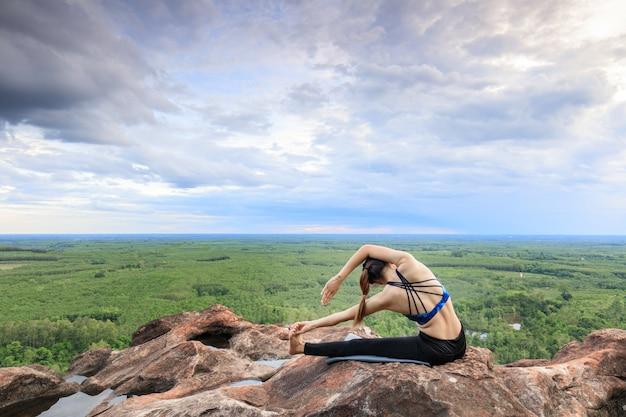 Asiatinnen spielen es yoga auf der gebirgsfelsenklippe.