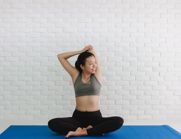 Asiatinnen spielen yoga zu hause mit weißem backsteinmauerhintergrund.