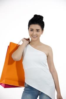 Asiatinnen und schönes mädchen hält einkaufstaschen und lächelt