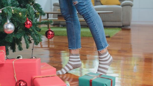 Asiatinnen verzieren weihnachtsbaum am weihnachtsfest. weiblicher jugendlich stand feiern weihnachtswinterferien im wohnzimmer zu hause.
