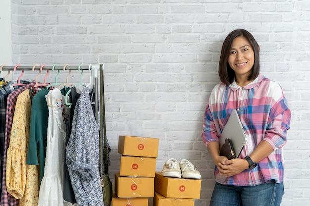 Asiatinnen, welche die laptop-computer online verkauft halten