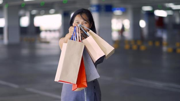 Asiatinnen zeigen taschen, die glücklich vom einkaufszentrum einkaufen gehen