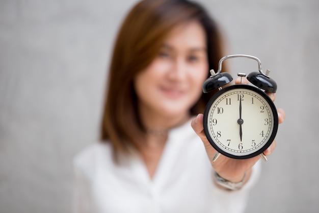 Asiatinnen zeigen uhrzeiten um 6 uhr, es ist zeit, etwas konzept zu tun