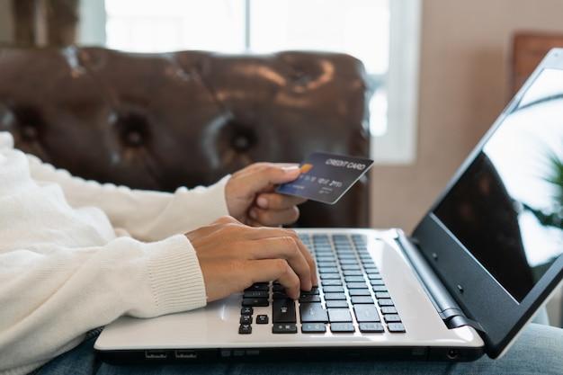 Asiatinon-line-einkaufen mit der kreditkarte und computer, die zu hause auf sofa, digitaler lebensstil mit technologie, e-commerce-konzept sitzen