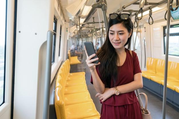Asiatinpassagier, der das soziale netz über intelligenten handy in den skytrain-schienen verwendet