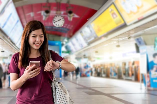 Asiatinpassagier, der die uhr am interexchange zwischen station von skytrain-schienen aufpasst
