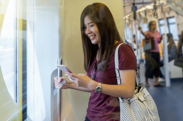 Asiatinpassagier mit dem zufälligen anzug unter verwendung des intelligenten handys in den skytrain schienen oder in der u-bahn