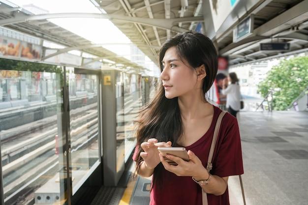 Asiatinpassagier mit der zufälligen klage unter verwendung des intelligenten handys in den schienen bts skytrain oder mrt