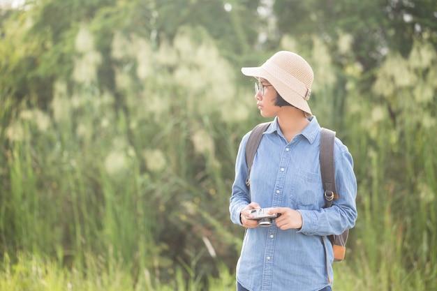 Asiatinphotographen benutzen filmkamera auf grüner unschärfe