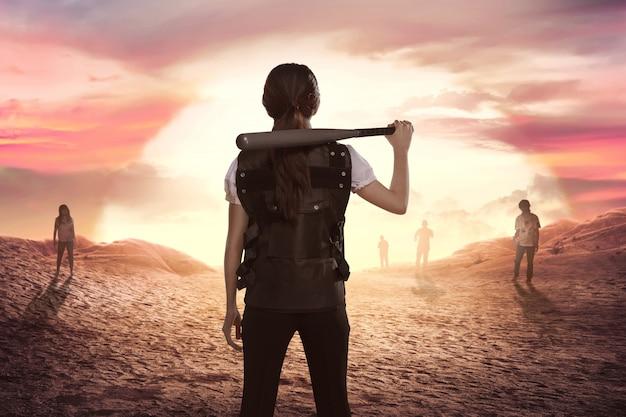 Asiatinpolizei mit baseballschläger in seiner schulter, die zombies betrachtet