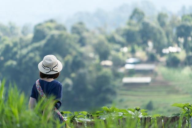 Asiatinreisender, der erstaunliche berge und himmel, reisefeiertags-entspannungskonzept betrachtet.