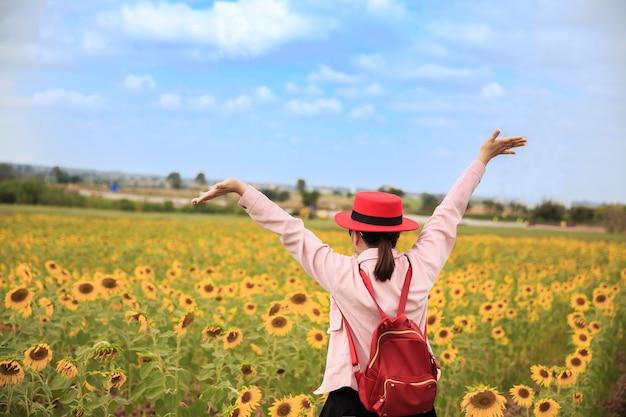 Asiatinreisender mit dem rucksack, der hut im sonnenblumengarten hält und erstaunlichen wald betrachtet.