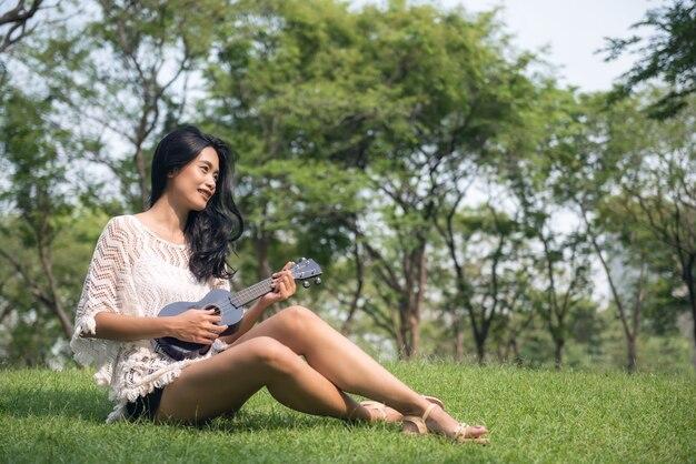 Asiatinspiel auf ukulele im garten