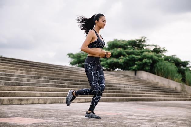 Asiatinsportfrau, die oben auf stadttreppe läuft