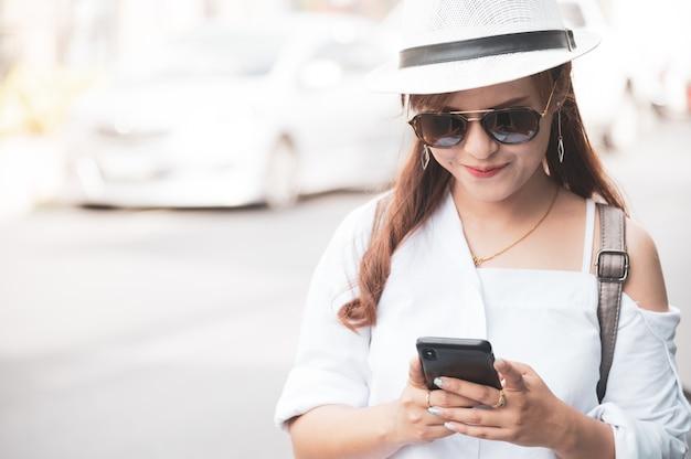 Asiatintourist überprüft simsenden smartphone auf straße und verwendet handy-app, um karte online zu überprüfen.