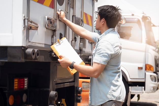 Asiatisch ein lkw-fahrer, der zwischenablage hält, prüft sicherheitsstahl-stahltür des container-lkw. fracht, logistik und transport.