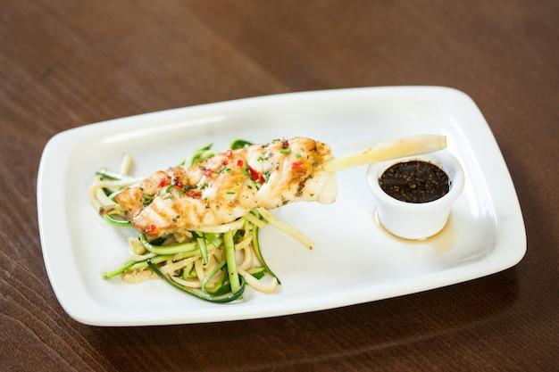Asiatisch inspiriertes fischgericht mit nudeln und julienne-gemüse