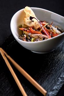 Asiatisch mit miso-nudeln, sojasauce, kräutern. auf einem schwarzen steintisch mit essstäbchen. draufsicht kopieren