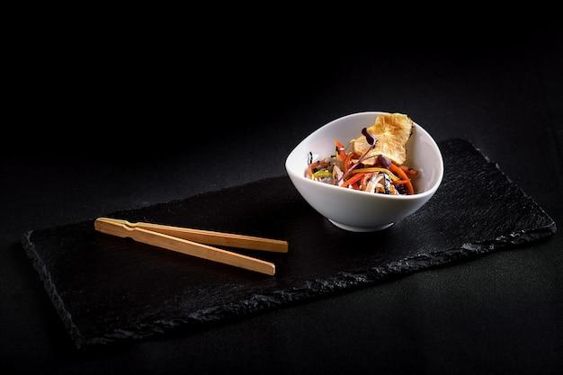 Asiatisch mit miso-nudeln, sojasauce, kräutern. auf einem schwarzen steintisch mit essstäbchen.