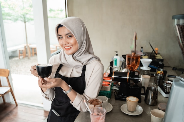 Asiatisch verschleierte kellnerin lächelnd halten eine tasse kaffee