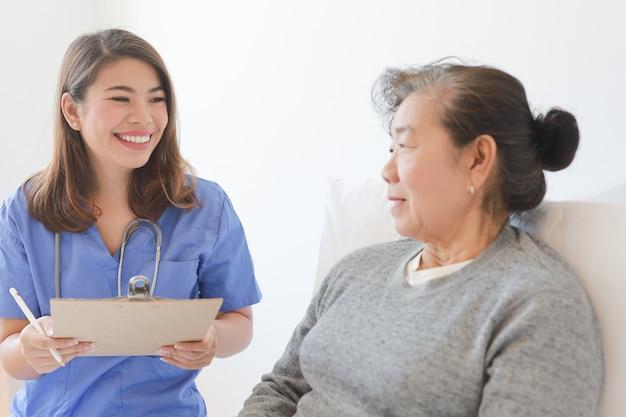 Asiatische ältere alte frau auf dem bett mit doktor und ihrem sohn im krankenhaus