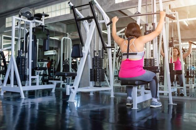 Asiatische ältere fette frau in der sportkleidung zurück trainierend mit maschine an der turnhalle.