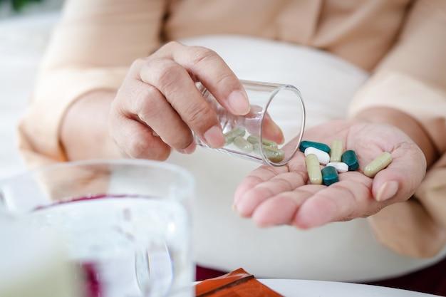 Asiatische ältere frau bleibt zu hause, um eine infektion zu verhindern während der coronavirus-epidemie erkrankte sie an fieber und nahm medikamente zur behandlung des virus ein. heimisolationskonzept, bleiben sie zu hause