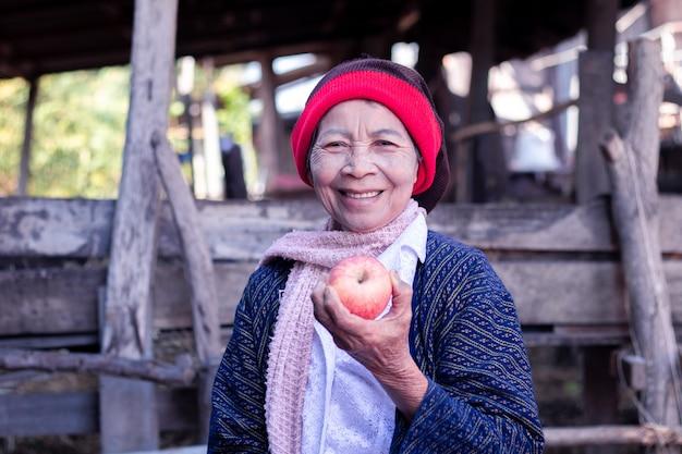Asiatische ältere frau, die apfel mit großem lächeln hält und isst