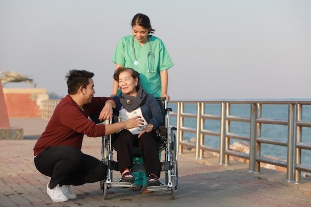 Asiatische ältere frau, die auf dem rollstuhl mit frau in der arztuniform im parkkrankenhaus sitzt