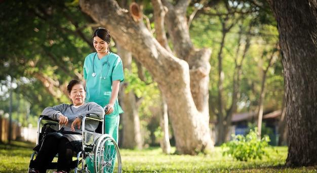 Asiatische ältere frau, die auf dem rollstuhl mit frau in der doktoruniform im parkkrankenhaus sitzt