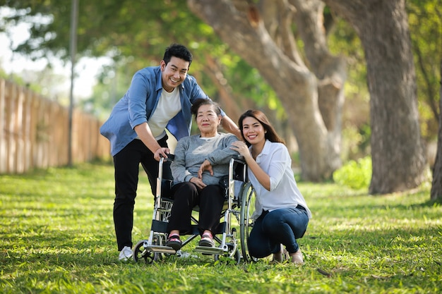 Asiatische ältere frau, die auf dem rollstuhl mit glücklichem lächelngesicht der familie auf dem grünen park sitzt
