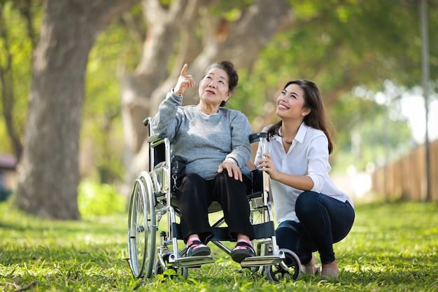 Asiatische ältere frau, die auf dem rollstuhl mit ihrem glücklichen lächelngesicht der tochterfamilie auf dem grünen park sitzt