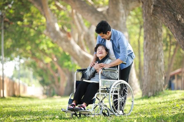 Asiatische ältere frau, die auf dem rollstuhl mit ihrem glücklichen lächelngesicht des sohns auf dem grünen park sitzt
