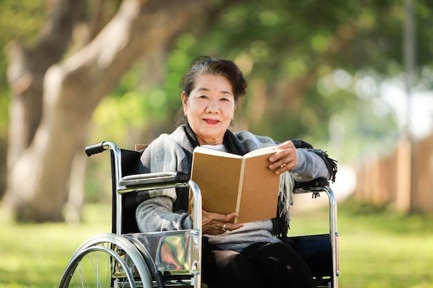 Asiatische ältere frau, die auf dem rollstuhl sitzt, der das buch im park liest
