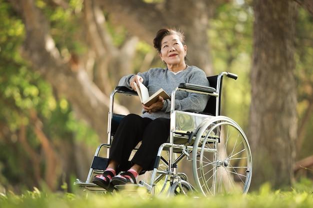 Asiatische ältere frau, die auf dem rollstuhl und dem lesebuch im parkgartenlächeln und im glücklichen gesicht sitzt