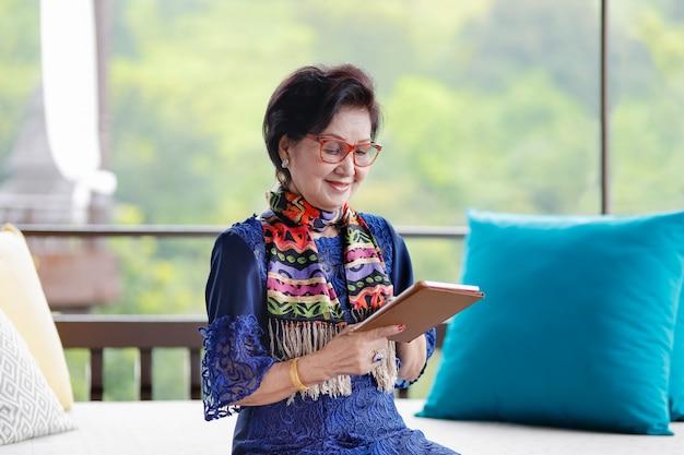 Asiatische ältere frau, die auf dem sofa sitzt und eine tablette verwendet