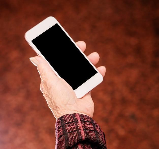 Asiatische ältere frau, die auf smartphone sitzt und schaut
