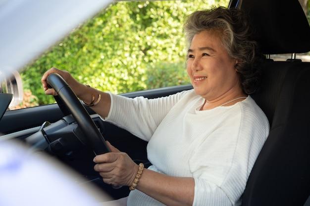 Asiatische ältere frau, die beim autofahren lächelt.