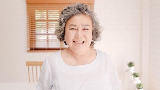 Asiatische ältere frau, die dem glücklichen lächeln und zur kamera schauen schaut, während sie sich auf dem sofa im wohnzimmer zu hause entspannen. lebensstil ältere frauen zu hause konzept.
