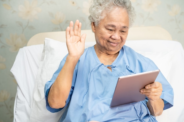 Asiatische ältere frau, die digitales tablett für videoanruf verwendet.