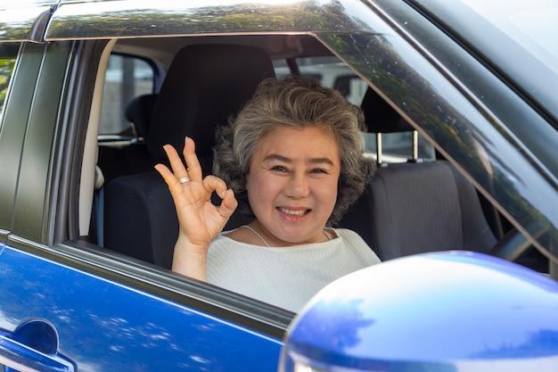 Asiatische ältere frau, die ein auto fährt, das ok mit freudigem positivem ausdruck während der fahrt zur reise zeigt, leute genießen lachenden transport und fahren durch konzept