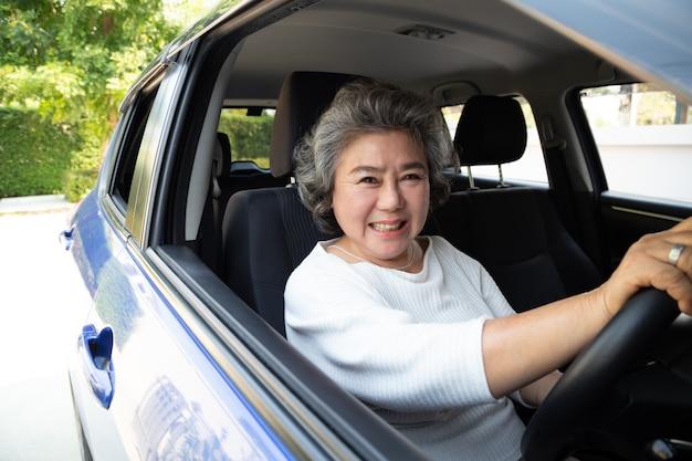 Asiatische ältere frau, die ein auto fährt und glücklich mit freudigem positivem ausdruck während der fahrt zur reise lächelt, genießen leute, transport zu lachen und durch konzept zu fahren