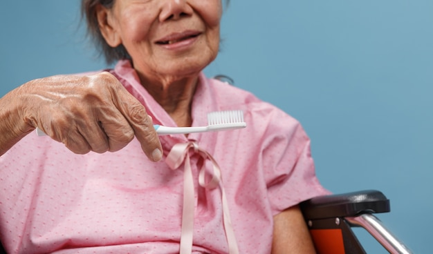 Asiatische ältere frau, die eine zahnbürste benutzt