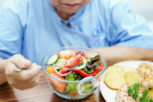 Asiatische ältere frau, die frühstücksgemüse gesundes essen isst.