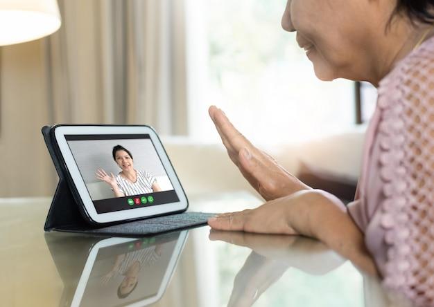 Asiatische ältere frau, die hand winkt und mit ihren verwandten und familie über internet und drahtlose technologie spricht.