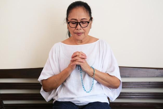 Asiatische ältere frau, die mit rosenkranz betet