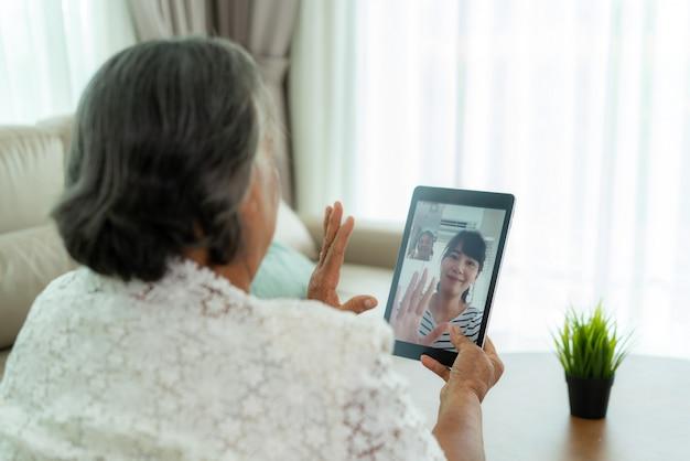 Asiatische ältere frau, die online mit ihrer tochter spricht