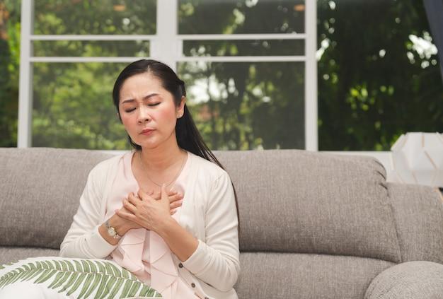 Asiatische ältere frau, die schmerz in der brust glaubt, während sie auf sofa im wohnzimmer zu hause sitzen