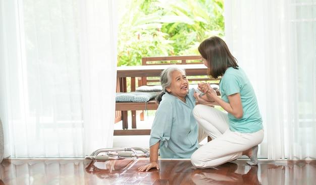 Asiatische ältere frau, die zu hause auf den boden fällt, nachdem sie vor der haustür gestolpert ist