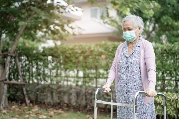 Asiatische ältere frau gehen mit gehhilfe und tragen eine gesichtsmaske, um coronavirus covid-19 zu schützen.
